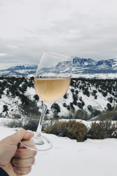 Holding a full glass of rosé wine in a beautiful, snow-covered mountain setting in Colorado.