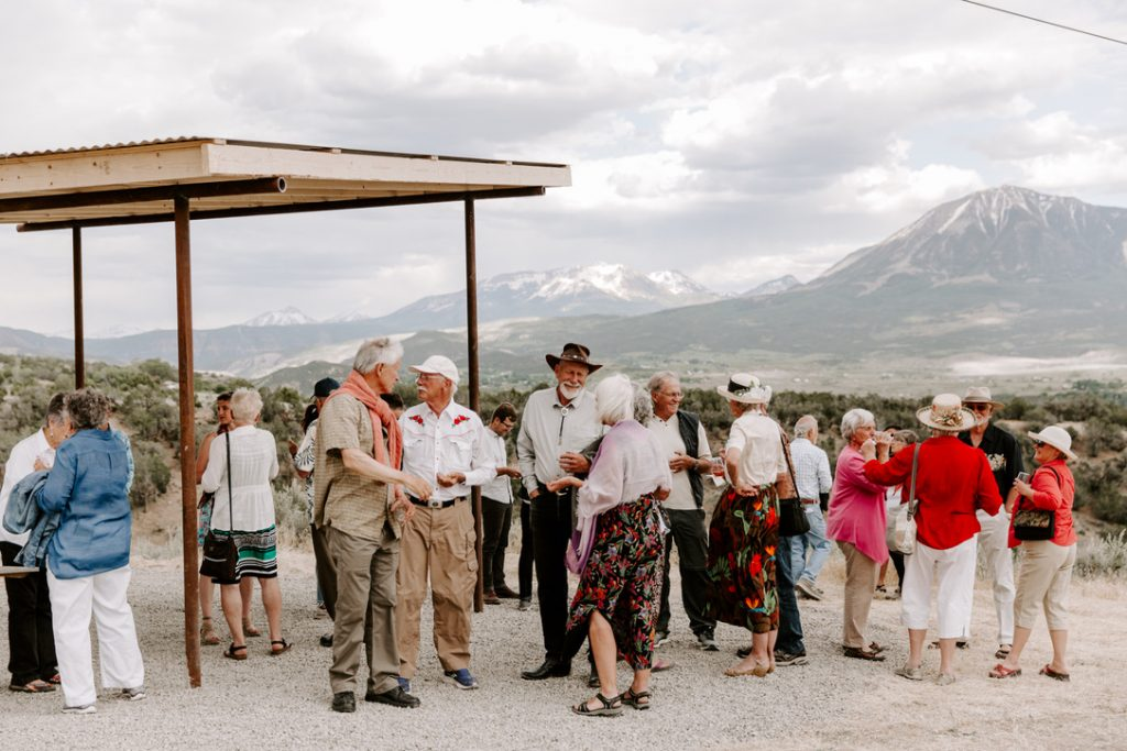 40 people gather underneath the new tasting overlook at The Storm Cellar winery in Hotchkiss, Colorado, overlooking the beautiful mountains of the West Elk Wilderness.